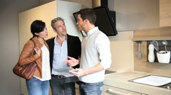 Kitchen furniture salesman giving advice to couple Stock Footage