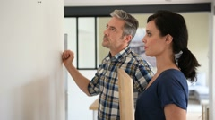 Couple at home hanging frame on wall Stock Footage