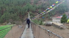 Man walking on suspension bridge in Nepal Stock Footage