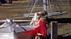 1958: Sister play on steel sturdy merry go round carousel park. - stock footage