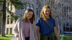 Two Happy Teen Girls Walk And Talk In City Park On Sunny Spring Day Stock Footage