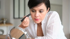 Middle-aged woman applying eye concealer in front of mirror Stock Footage