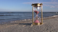 Hourglass with pink sand by the sea Stock Footage
