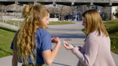 Friends Share Headphones, Listen To Music, As They Walk Through City Park Stock Footage