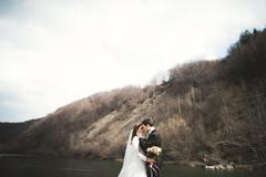 Happy wedding couple, bride and groom posing neat river against backdrop of the - stock photo