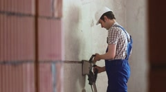 The man makes the grooves in the wall using wall chasers - stock footage