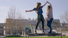Teen Girls Listen To Music From Smartphone, And Dance Together On Park Bench - stock footage