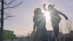 Fun Teens Dance In Park, One Stands On Bench, Twirls Her Friend Stock Footage