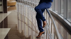 Businessman standing by banisters and calling with walking people on background Stock Footage