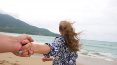 Woman holding man hand smile on beach ocean leads summer vacation follow tourist - stock footage