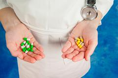Pharmaceutical colorful capsules in doctor's hands - stock photo