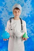 Young boy in doctor's costume holding enemas - stock photo