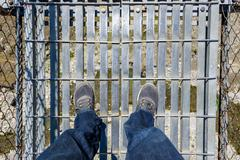 Looking down on a suspension bridge - stock photo