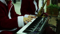Musical band in Santa Claus suits playing merry melody to create Xmas atmosphere - stock footage