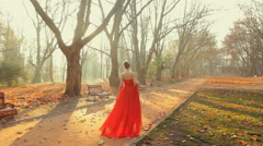 Beautiful young lady wearing amazing red dress walk on the park in autumn Stock Footage