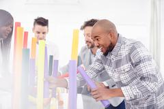 Colleagues in team building task balancing colourful tubes smiling Stock Photos