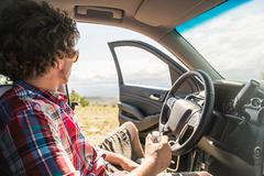 Young man looking out at landscape from off road vehicle, Bridger, Montana, USA Stock Photos