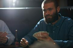 Male friends playing card game at traditional uk pub - stock photo