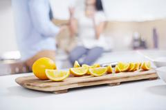 Quartered oranges on kitchen counter in front of young couple - stock photo