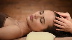 Hair care in spa salon. Massage of the head for young woman Stock Footage