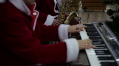 Happy musicians performing Christmas songs on piano and saxophone at concert - stock footage