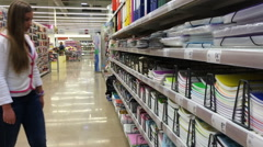 Young woman chooses stationery in a supermarket - stock footage
