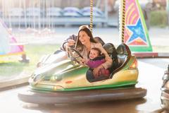 Mother and daughter in bumper car at fun fair - stock photo