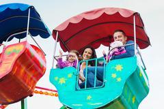 Father, mother, daughters enjoying fun fair ride, amusement park Kuvituskuvat