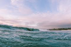 Distant view of surfer on ocean wave near coast, Encinitas, California, USA Kuvituskuvat