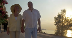 Senior couple walking on sea-front at sunset Stock Footage