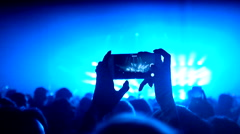 Fans waving their hands and hold the phone with digital displays Stock Footage