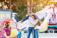 Parents at fun fair, waving their child taking ride Stock Photos