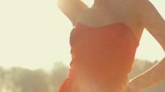 Young beautiful professional model posing on camera in a red long dress Stock Footage