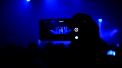 Fans waving their hands and hold the phone with digital displays - stock footage