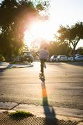 Young man skateboarding in road, rear view, Corona, California, USA Stock Photos