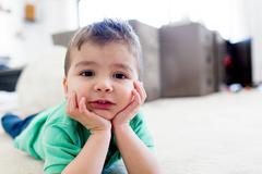 Preschool boy lying on carpet chin in hands, resting on elbows, looking at ca Stock Photos
