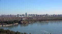 East causeway of the iced Kunming lake with the Beijing skyline on background Stock Footage