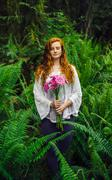 Young woman holding bunch of pink gerberas amongst forest ferns Stock Photos