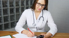Beautiful young female doctor sitting in front of working table holding jar of Stock Footage
