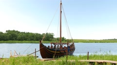 Traditional Viking longship boat, Karvi, stand at green river shore - stock footage