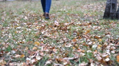 Woman walking on the ground with autumn leaves Stock Footage