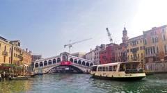 Waterbus and gondolas under the Rialto Bridge in Venice, Italy. Stock Footage