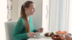 Young woman with a cup of coffee. Breakfast at the girl. Women drinking coffee Stock Footage