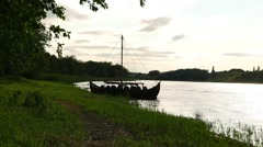 Viking boat stand at river shore, black silhouette at back light Stock Footage