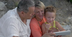 Child enjoying pad game with grandparents Stock Footage