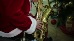 Man wearing Santa suit playing Xmas carol song on saxophone at festive concert Stock Footage