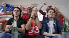 4K Excited group of friends watching American football game on TV & cheering - stock footage