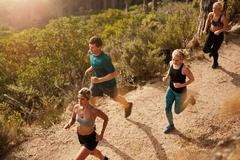 Active young people running on mountain trail Stock Photos