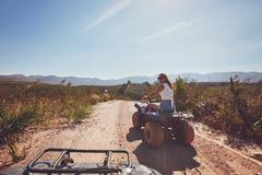 Young woman on an all terrain vehicle in nature - stock photo