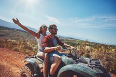 Young couple enjoying quad bike ride Stock Photos